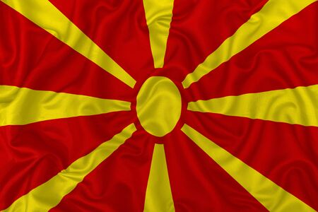 North Macedonia country flag on wavy silk textile fabric background.