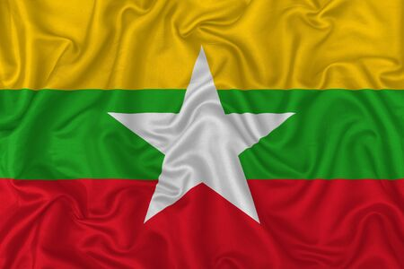 Myanmar country flag on wavy silk textile fabric background. 版權商用圖片
