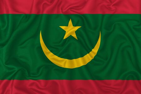 Mauritania country flag on wavy silk textile fabric background.