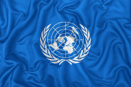 United Nations flag on wavy silk textile fabric background.