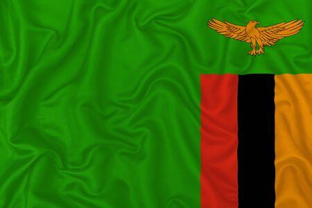 Zambia country flag on wavy silk textile fabric background. 版權商用圖片