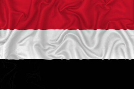 Yemen country flag on wavy silk textile fabric background.