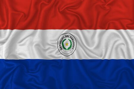 Paraguay country flag on wavy silk textile fabric background.