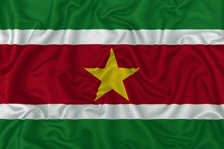 Suriname country flag on wavy silk textile fabric background.