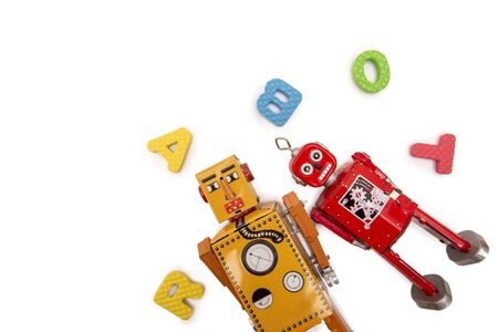 Close up view of colorful vintage tin robot toys with foam letters.