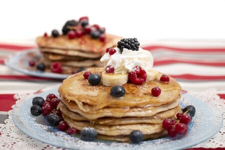 Delicious oats and banana pancakes with mixed berries fruits and sugar powder dripping with honey.