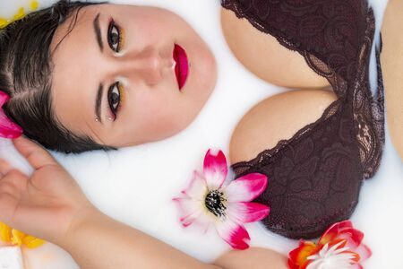 woman wearing sensual red lingerie on a milky bathtub with flowers.