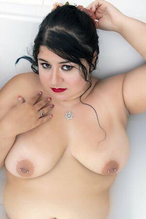 beautiful sensual woman nude posing in a milky bathtub.