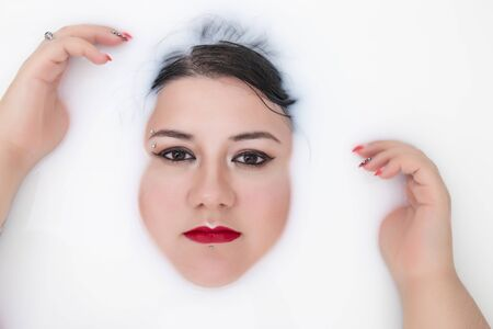 woman face closeup half submerged on milky bathtub. Banco de Imagens