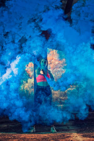 Girl maneuvering colorful smoke grenade on a abandoned factory.