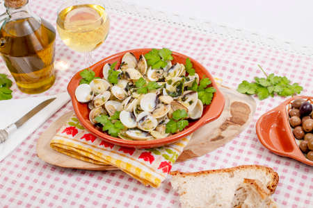 Typical starter portuguese meal of clams with garlic, olive oil and parsley.