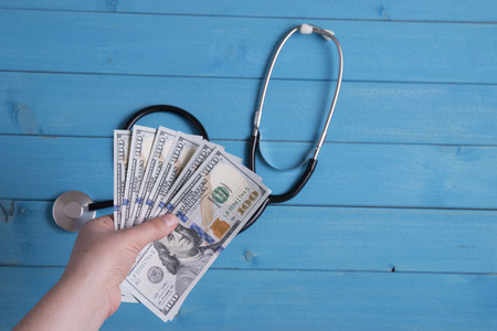 hospital fees: hand hold money and stethoscope