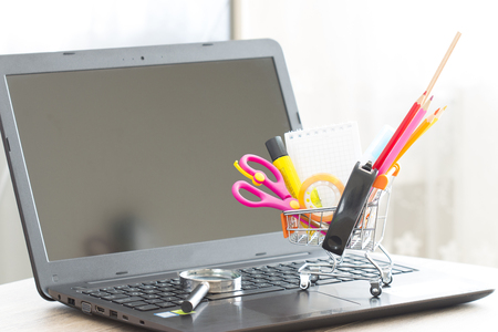 marketing online: School and stationery material in shopping cart top laptop Stock Photo