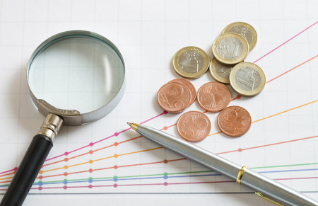 magnifier and coins on the graphic