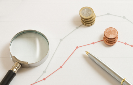 magnifier and coin on the stock market paper