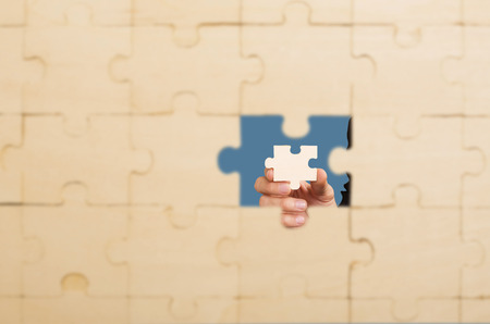 hand places the last piece of the puzzle