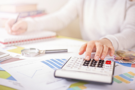 woman is doing calculations on office desk 스톡 콘텐츠