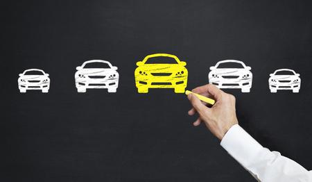 Mann, der gelbes Auto auf Tafel zeichnet Standard-Bild