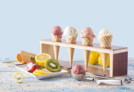 Variedades de helados en corneta con frutas sobre mesa azul Foto de archivo