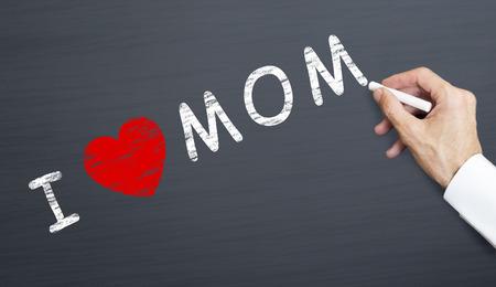 hand writing i love mom on blackboard with chalk