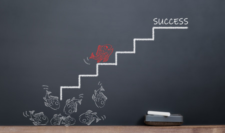 red fish climbing out of stairs to success