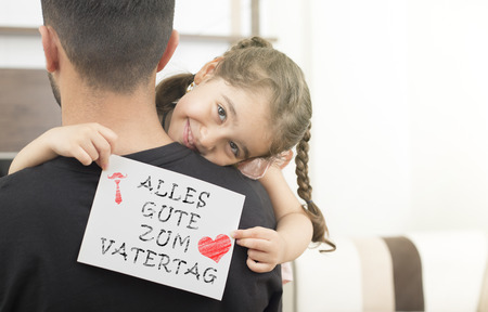german lettering, fathers day happy birthday message.little girl hugging her father and showing the message of congratulation Imagens