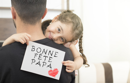 French text, Happy Fathers Day message. Girl hugging her father and showing fathers day celebration message