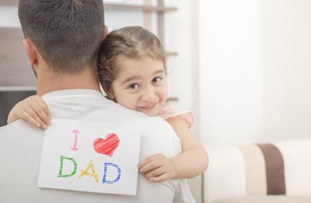 girl shows love dad card on her dads shoulder