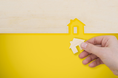 hand places a model house on yellow background.