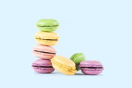 Macarons stacked in a row isolated on blue background