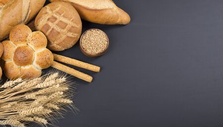 different kinds of bread and wheat ears on black background