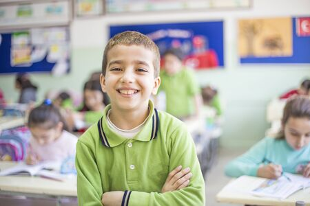 Portrait of ten years old male student. smiling standing in classroom Imagens