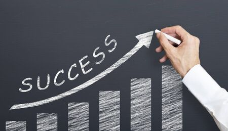 man is drawing success graph on chalkboard. success concept Imagens