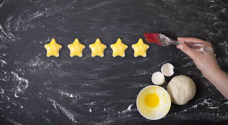 five star customer rating survey. Woman is painting her stars from dough with eggs on yellow