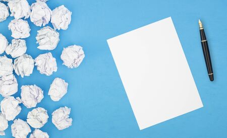 blank white paper and pencil beside crumpled paper balls Imagens