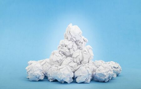 crumpled white paper balls on blue background