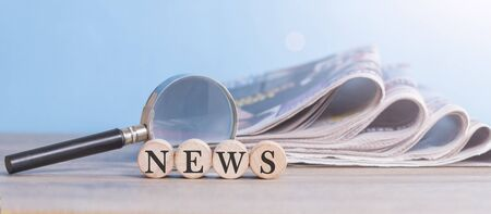 writes news on wooden cube with newspaper stack and magnifying glass  Foto de archivo