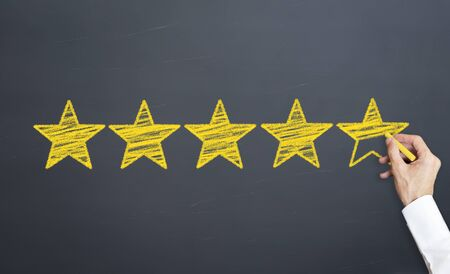 five yellow stars drawn with chalk on black chalkboard. customer voting concept
