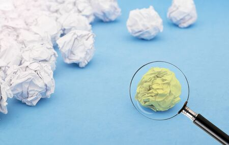 crumpled yellow paper ball, examining with magnifying glass Imagens