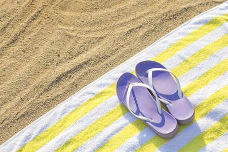 purple slippers on yellow towel on beach background