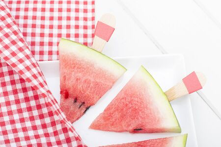 stick triangular watermelon slice and red plaid picnic cloth.
