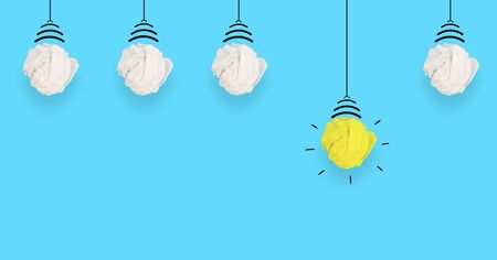 idea concept with crumpled paper. Yellow lamp on blue background