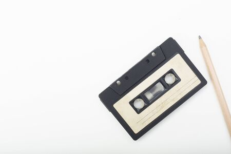 old audio cassette and pencil on white background