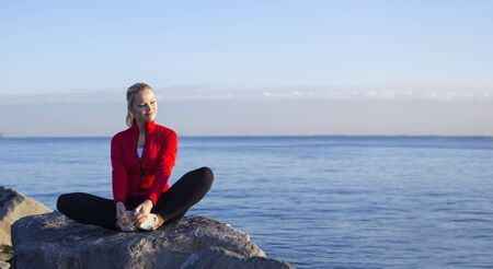 young blonde woman in sport dress is doing exercise sitting at seaside