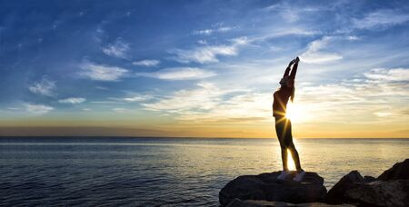 Silhouette of woman with arms up at the seaside. meditating girl