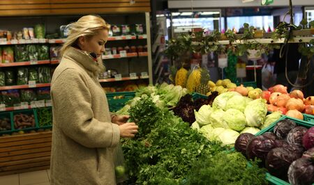 young housewife chooses vegetables in vegetable shop at the supermarket 版權商用圖片