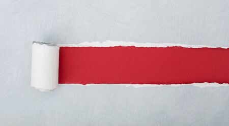 torn gray paper over red background 스톡 콘텐츠