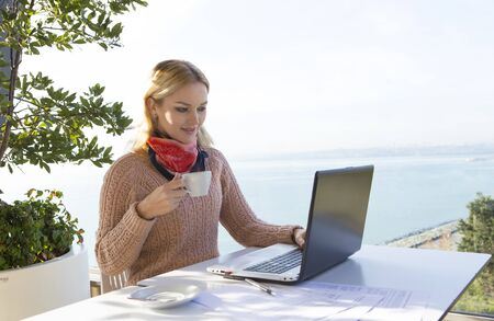 business woman working on laptop while drinking coffee outside