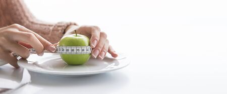 woman measures the circumference of the apple with tape measure
