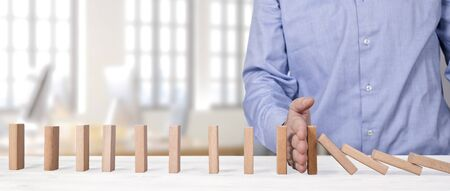 businessman stopping falling wooden blocks with his hand. domino effect intervention concept